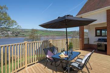 This immense decked area is kitted out with a huge gas barbecue, bubbling hot tub, and several seating areas. Perfect for watching the children play on the lawn below.