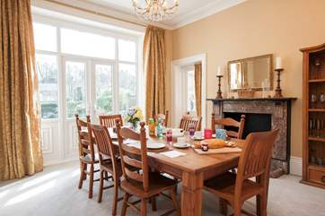 The stunning dining-room has a large table seating 8 with patio doors opening up to the garden and pool area