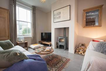 The cosy living-room features a wood-burning stove, perfect for the winter months.