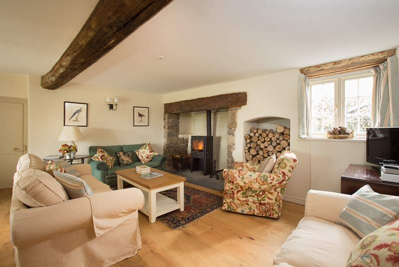 The sitting-room with its wood-burning stove is at the heart of the house. There is plenty of comfortable seating for you all to relax.