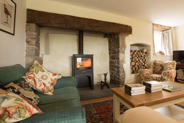 The wood-burning stove is a real focal point in this room - as is the alcove stacked full of logs for you.