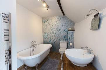 The en suite bathroom is fabulous, with its roll-top bath, hand-made basin surround and hand designed feature wall!
