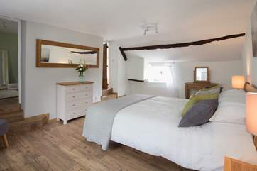 The en suite bathroom is up the steps to the right and to the left, also up some steps, is a cot room or dressing-room.