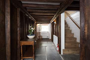 This is the original cross-passage with its historic panelling. A stable-door takes you out to the back garden. There is a cloakroom to the right and then the wooden stairs to the first floor.