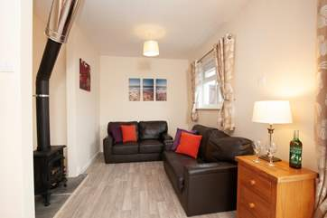 The cosy living area features a log burning stove, ideal for Autumn breaks