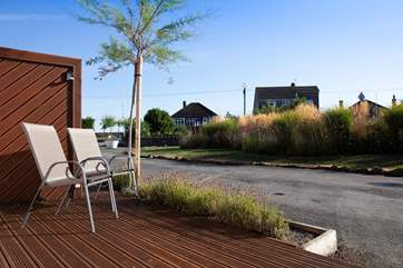 Relax on the decking a mere stones throw from from the sea front