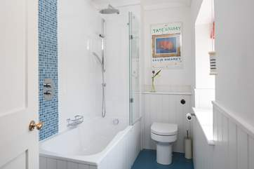 A bath and shower in this bright family bathroom.