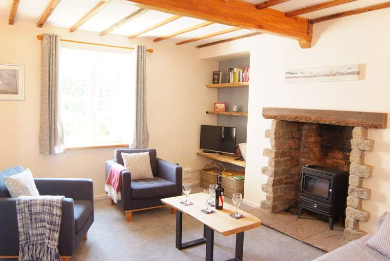 The sitting-room has the character of a beamed ceiling and stone fireplace with the comfort of an electric wood-burner effect stove and contemporary furnishings.