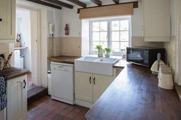 The kitchen looks out onto the patio-area, the  utility-room is to the left and the back door to the garden.