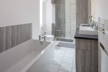 The stylish family bathroom has a double shower and very large bath.