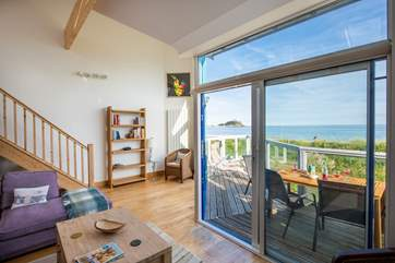 French windows lead out from the living area to the balcony and, across the railway line is the sea.