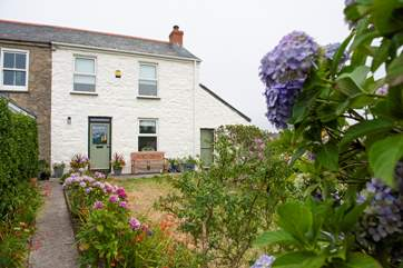 An enclosed front garden leads to the cottage.