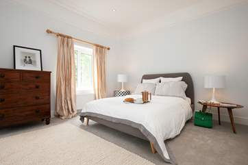 The master bedroom is very stylish with views over the rear garden