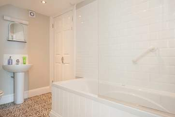 The spacious family bathroom with bath and shower over