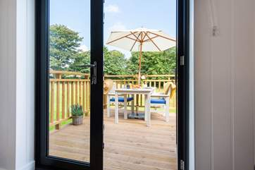 Looking out the patio doors to the deck and meadow beyond.