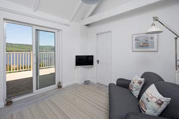 The sitting-room is perfect for four, and even more perfectly placed to step out onto the decked area to soak up the amazing views, or oversee the barbecue sizzling away.