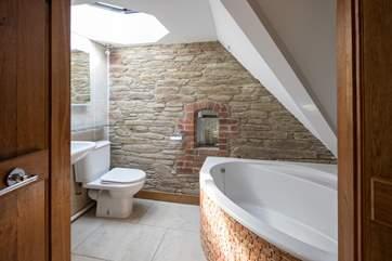 En suite to bedroom 3 boasts this beautiful corner bath and eye-catching brickwork.