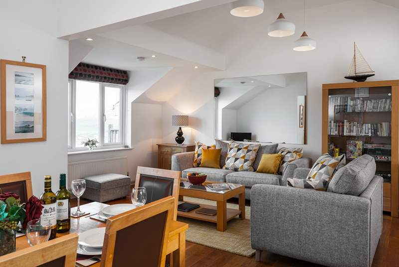 The open plan living area has sunlight flooding in, you can see views of Porth Beach to the side, from the sitting room.