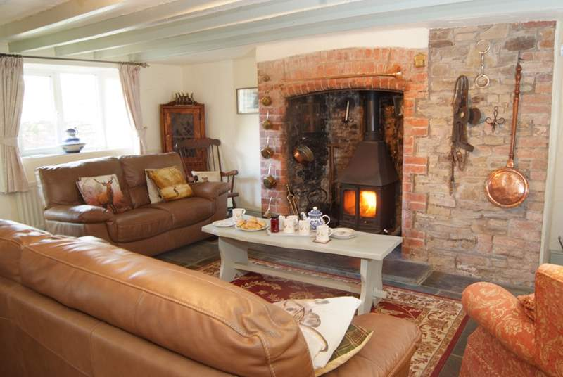 The inglenook fireplace with wood-burning stove is at the heart of this welcoming homely cottage.