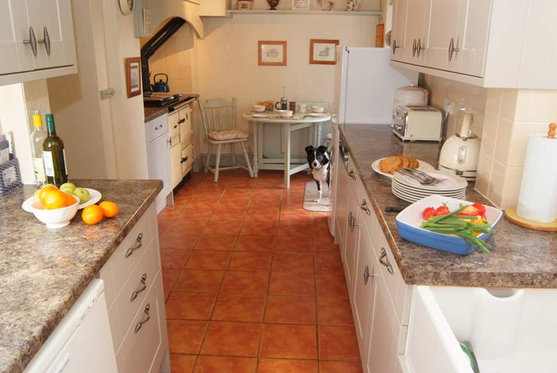 The galley style kitchen has space for a breakfast table next to the lovely warm Rayburn, and French windows out to the garden.