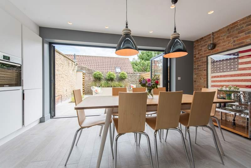 The open plan kitchen/dining-room with the light pouring in from the garden.