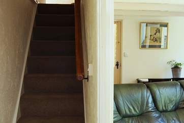 A typical cottage staircase leads from the sitting-room to the first floor bedrooms and bathroom.