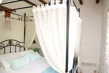 A four-poster adds charm to the bedroom.