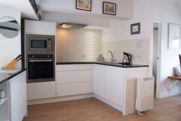 The fabulous new kitchen is very well-equipped with a built-in microwave, oven and hob.