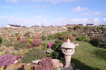 The raised lawn at the back of the house is set in heather borders.