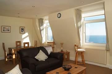 The light, sunny sitting/dining-room has wonderful sea views.