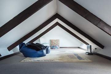 The galleried den up under the eaves is accessed via a wooden ladder from the sitting room, The beanbags are great for children to lounge on and watch television.