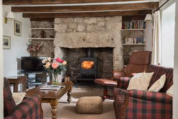 The cosy front sitting-room also features a welcoming wood-burner.