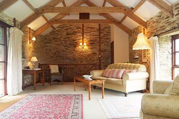 The spacious open plan living-room has a wonderful high apex ceiling showing the lovely old beams.