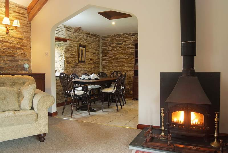 The lovely wood-burner in the sitting-area, looking through into the dining-area.