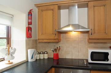 The kitchen is small but well-equipped, with lovely garden views.