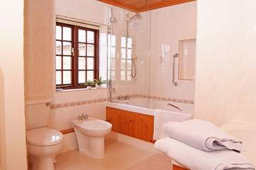 There is a really large family bathroom with bath and shower.